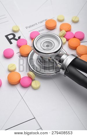 Prescription Or Rx Form With Medical Stethoscope, Pills And Pen On The Doctors Desk