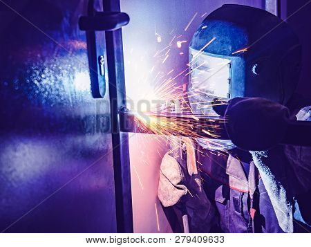 Welder Worker Performs Jump Welding. Worker Welder Performs Arc-welding Process Of Metal Structures.