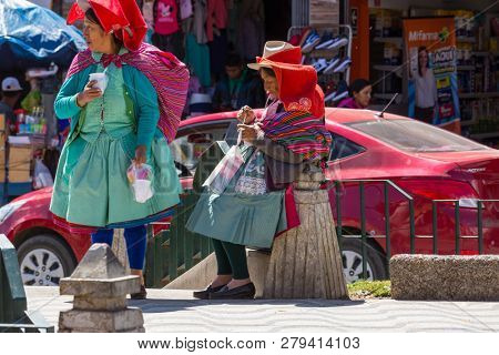 HUARAZ, PERU - JULY 27: Traditionally dressed peruvian people sell fruits and vegetables on the street market on July 27, 2017 in Huaraz, Peru.