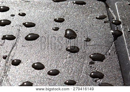 Rain Drops On A Table Top Create A Bevy Of Miniature Starbursts