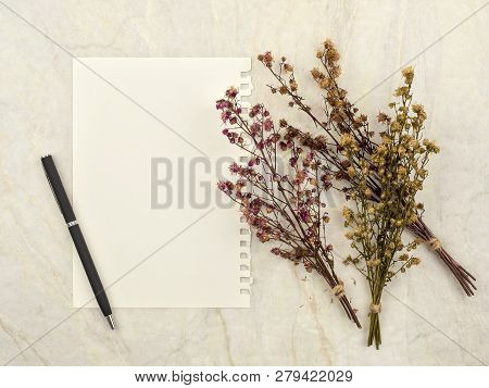 Top view of note pad paper with pen and group of bouquet dried and wilted multiple color Gypsophila flowers on matt marble background for text, letter, message or verse poster