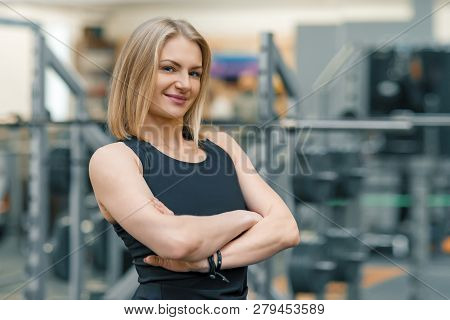 Portrait Of Adult Blonde Fitness Woman Personal Trainer With Folded Hands In The Gym, Beautiful Smil