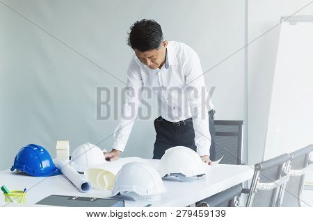 Business Engineering Man Looking Project Constructed Paper Blueprint Plans At Construction Site In T