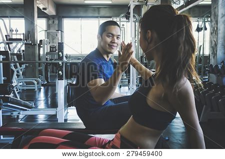 Fitness Man And Woman Giving Each Other A High Five After The Training Session In Gym. Fit Couple Hi