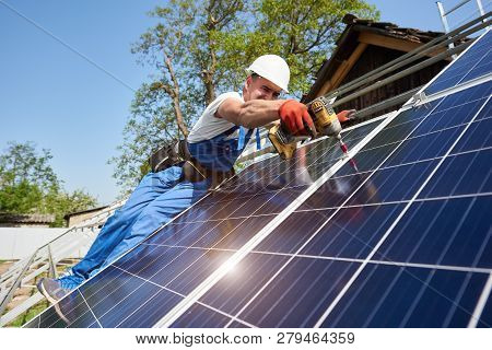 Technician installing solar photo voltaic panel to metal platform using screwdriver on bright blue sky background. Stand-alone solar panel system installation concept. poster