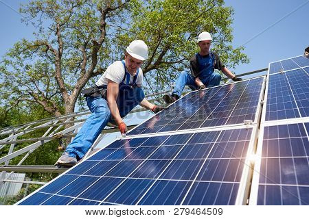 Two Young Technicians Installing Heavy Solar Photo Voltaic Panel On Tall Steel Platform On Green Tre