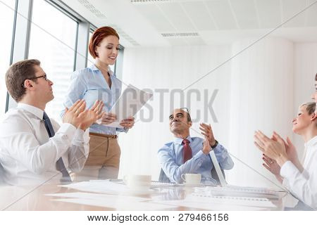 Colleagues applauding businesswoman standing with document in boardroom at office during meeting