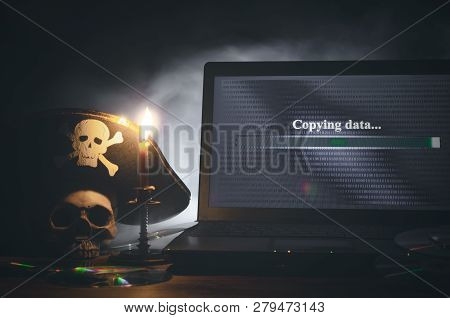 Illegal Data Copying Concept. Cybercrime. Computer Piracy Background. Pirate Hat, Human Skull, Lapto