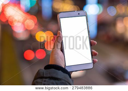 Woman Holding A Smartphone With A Blank White Screen At Night With Lights From Car Traffic In The Ba