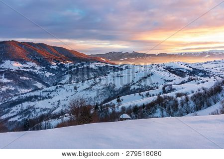 Winter Sunrise In Mountains. Beautiful Carpathian Countryside. The Sky Is On Fire. Rural Area With R