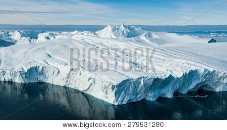 Global Warming and Climate Change - Giant Iceberg from melting glacier in Ilulissat, Greenland. Aerial drone of arctic nature landscape famous for being heavily affected by global warming.
