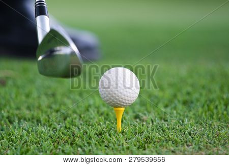 Close-up View Of A Golf Ball Set On A Wooden Golf Tee In The Grass With A Golf Club Positioned Behin