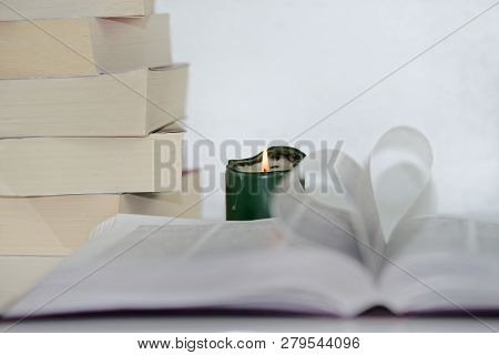 Heart Shape From Paper Book Against Focused Green Candle And Pile Of Books. Love For The Books