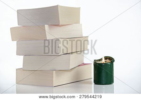 Composition Of Green Burning Candle And Pile Of Books Against White Background