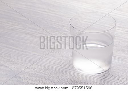 A Close-up Image Of A Wet Steaming Glass Of Water Half Full. On A White Wooden Table, And When The S