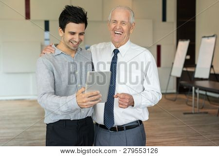 Laughing Colleagues Looking At Tablet. Senior Businessman Smiling And Supporting His Young Employee.