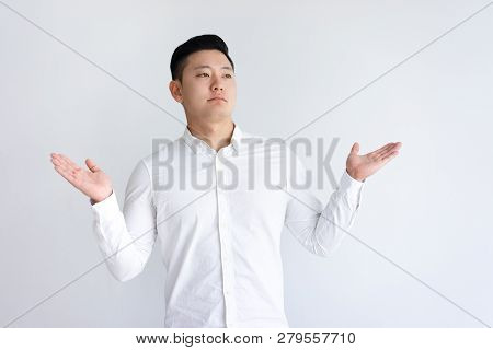 Uncertain Asian Man Throwing Up Hands And Looking Away. Young Guy Standing And Doubting. Confusion C