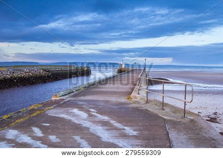 Seaside Pier In The Town Of Nairn, Scotland. The Concrete Pier Forms The Entrance To The Harbour.
