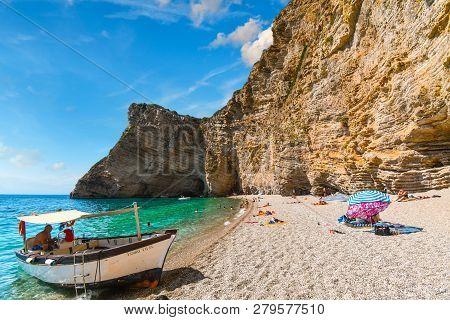 Corfu, Greece - September 18 2018: A Small Boat Waits On The Sandy Beach To Transport Tourists Back