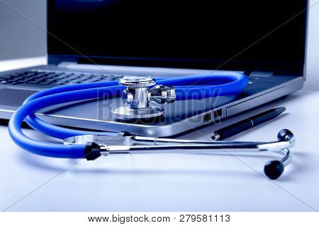 Workplace Of Doctor With Laptop, Stethoscope And Rx Prescription On White Table. Top View.
