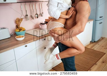 Cut View Of Sexy Bodies In Kitchen. Young Man Hold Woman With Hands.