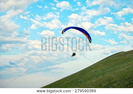 Trike With A Parachute Against The Blue Sky. Paragliding Flying Over The Clouds