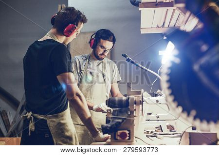 Two attractive young men in aprons and earmuffs standing near workbench in brightly illuminated workshop and working with wood together poster
