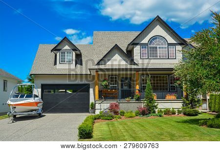Suburban House With Landscaping In Front And Blue Sky Background. Light Powerboat Parked On Concrete