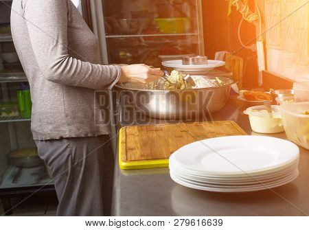 A Cook In The Kitchen Weighs Portions Of Salad On Scales In Grams And Serves To The Table, Kitchener
