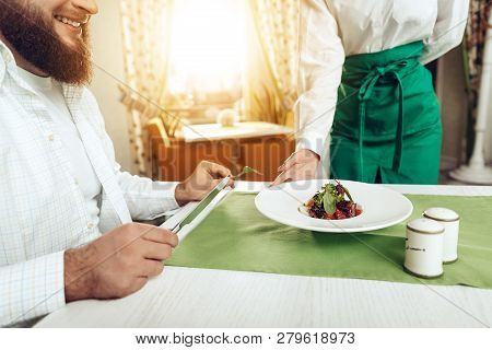 Girl Waiter Serves His Dish In Restaurant To A Man. Close Up Of Bearded Smiling Man Waiting Dish In
