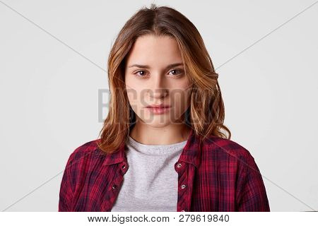 Headshot Of Serious Woman Has Confident Expression, Wears Checkered Shirt, Casual T Shirt, Stands Ag