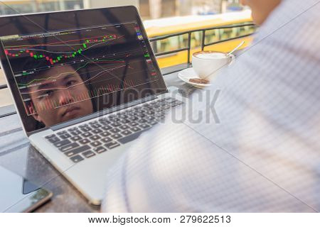 Asian Investor Watching The Change Of Stock Market On Laptop.