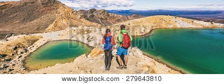 New Zealand volcanic mountain landscape in Tongariro Alpine Crossing National Park. Young people couple hikers tramping in NZ travel adventure, panoramic banner background.
