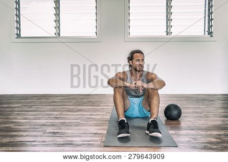 Gym workout man training floor exercises with weighted slam ball or medicine ball taking a break tired sweating thinking of disappointment.