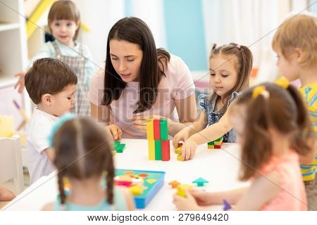 Kids Playing With Educational Toys At Table In Kindergarten. Nursery Teacher Looking After Children