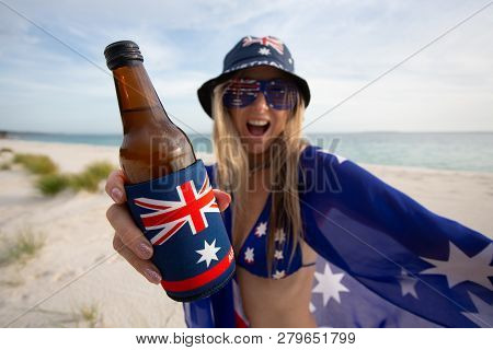 A Revelling Woman Holding A Beer On The Beach Celebrates Australia Day Or Supports Australian Sport