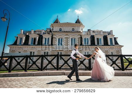 Russia, Orenburg  - July 29, 2017: The Bride And Groom Holding Hands Walking Near The Beautiful Buil