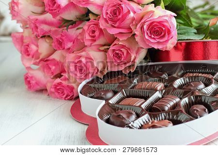 Dozen Soft Pink Rose Flowers With A Heart Shaped Box Of Chocolate Candy For Valentine Day Over A Woo