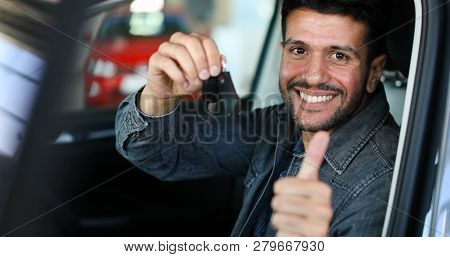 Positive young man holding a key sitting in a car with thumb up