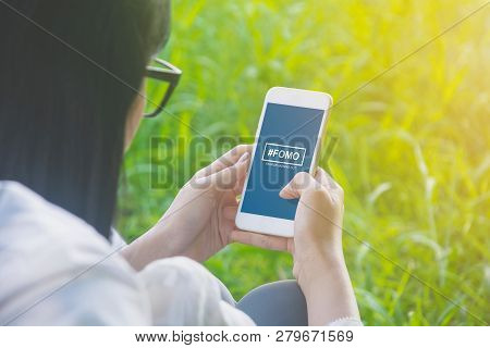 Fomo, Fear Of Missing Out Concept. Female Hand Holding Smartphone