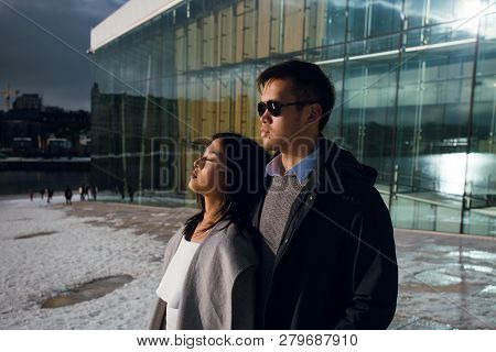 Sensual Asian Couple Wearing Stylish Winter Clothes Standing Outoors Near The Modern Building And Lo