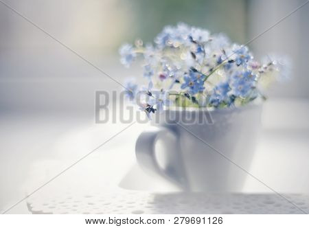 Blue Flowers Of A Forget-me-not In A White Cup In A Window On A Lacy Tray.
