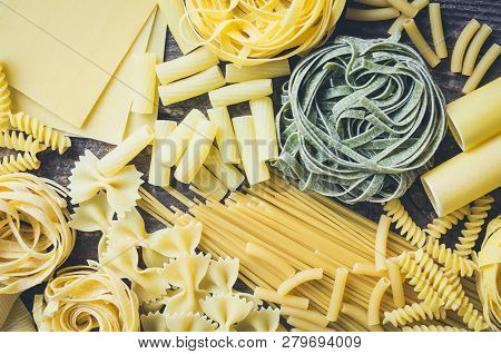 Background Texture From Variety Of Types And Shapes Of Italian Pasta On Old Wooden Background From A