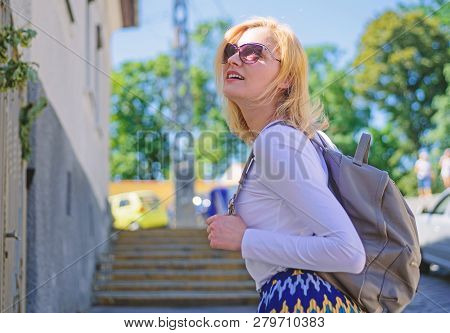 Urious Tourist. Trendy Girl Walking. Woman Carrying Backpack While Standing Outdoors. Girl With Styl
