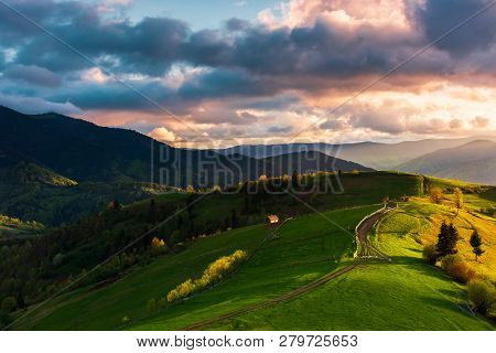 Wonderful Countryside In Mountains At Sunset. Path Through Grassy Hill. Cloudy Purple Sky. Beautiful