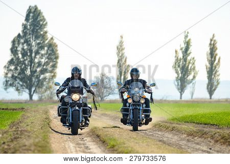 Two Motorcycle Drivers Riding Custom Chopper Bikes Together on an Autumn Dirt Road in the Green Field. Adventure Concept.