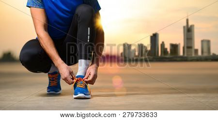 Young Male Sportsman Tying Running Shoes and Preparing for the Run at Sunset. Rest from Urban Lifestyle and Active Sport Concept.