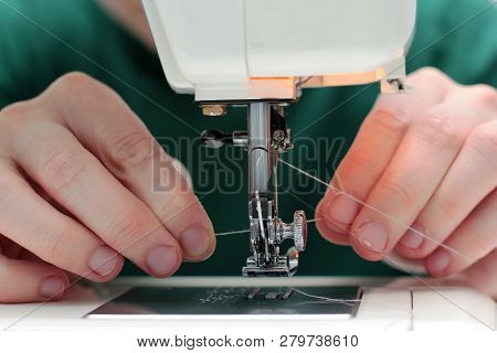 Close-up Seamstress Hands Working On Sewing Machine At Home. Sewing Process. Woman Hands Behind Sewi