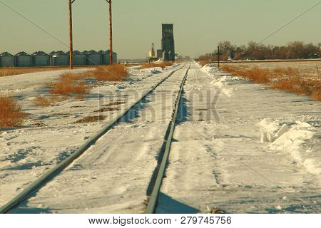 A Winter Scene Of Railroad Tracks Going By A Elevator  In A Small Town In Eastern North Dakota.