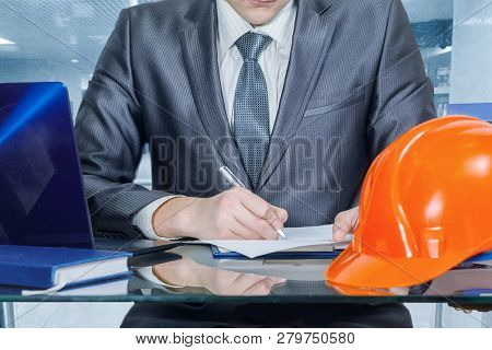 A Closeup Of An Engineer Or An Owner Of A Building Company Signing Documents While Sitting At The Gl